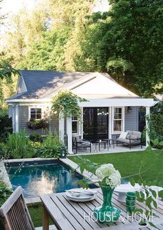 A traditional square-shaped pond gives this outdoor space a dreamy feel.   Photographer: Stacey Brandford   Designer: Lloyd Ralphs Design