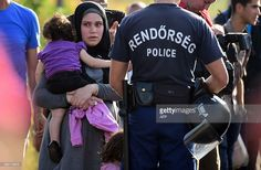A migrant mother watches the last migrant family crossing the border line between Hungary and Serbia near Roszke on September 14, 2015 as the border fence with Serbia was closed by Hungarian police this afternoon. Hungary has effectively stopped registering thousands of migrants crossing the border from Serbia and is transporting them straight to the Austrian frontier, the UN refugee agency said today. AFP PHOTO / ATTILA KISBENEDEK