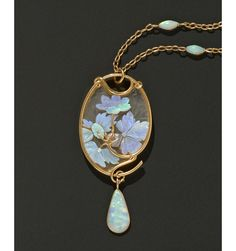 An Art Nouveau carved opal and engraved glass pendant by René Lalique mounted in gold, presented in its original gilded leather case. Paris, c1900.