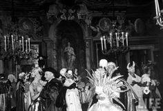 Guests fox-trotting around Palazzo Labia's upstairs ballroom, with Mrs Jacques Fath (R, Fore, back to camera) dressed as the sun.  Venice, Italy  September 1951  Photographer: Cornell Capa  © Time Inc.