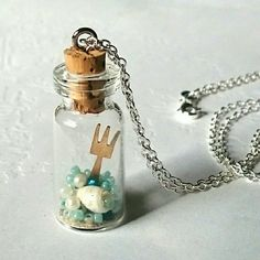 """Handmade necklace little Mermaid glass bottle Inspired by Disney's Little Mermaid!   Handmade by me (: totally unique and one of a kind! In the glass bottle includes:   - dingle hopper (fork)   - sand   - ocean water (blue beads, not actual water)   - sea shell   - pearl beads   (bottle is glued shut to make sure you don't lose any treasures!)   Silver chain is about 27"""" long Jewelry Necklaces"""
