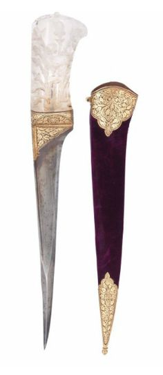 A ROCK CRYSTAL-HILTED DAGGER (PESH-KABZ)   NORTH INDIA, 19TH CENTURY   The blade of typical straight single-edged form tapering towards the point, the reinforced point of square section, the forte and base of the hilt with possibly later gold-damascened decoration, the hilt deeply carved to receive inlay work now lacking, with motifs of birds in foliage, the velvet covered sheath with gold-damascened mounts, some corrosion  14¾in. (40cm.) long with sheath
