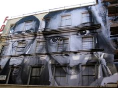 JR, a semi-anonymous French street artist, uses his camera to show the world its true face, by pasting photos of the human face across massive canvases.