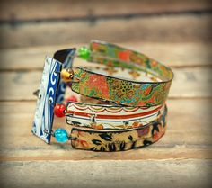 This one-of-a-kind triple bangle set was created from recycled and vintage tin in beautiful floral prints. The tin has been hand cut, sanded, and