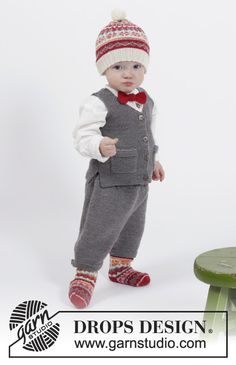 """Set consists of: Knitted DROPS vest with pockets and V-neck in """"Baby Merino"""", knee pants in stocking st in """"Baby Merino"""" and knitted hat and socks with Norwegian pattern in """"Fabel"""" and bow in garter st in """"Fabel"""". SIZE 1 months - 6 years. ~ DROPS Design"""
