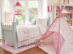 A mini tent serves as a cute clubhouse and venue for indoor campouts. Plus, it beautifully coordinates with the sweet pink tones of the bedding and hanging birdcage.