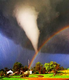 During 2005 in Kansas, storm chaser Eric Nguyen photographed this budding twister. By coincidence, the tornado appears to end right over a rainbow. Streaks in the image are hail being swept about by the high swirling winds.