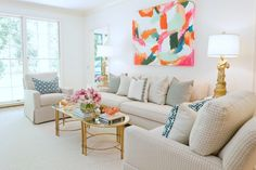 An oversized canvas adds the perfect pop of color in this light and elegant living space.