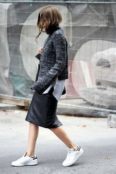 sweater layered over a shirt layered over a leather midi skirt and stan smith sneakers
