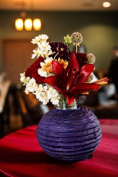 small red and purple centerpieces - what a great idea to stick a vase inside a paper lantern! love it!