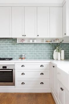 tiles Countertops White shaker drawers accented with dark nickel cup pulls are topped with a white marble countertop and positioned beside a stainless steel oven located beneath an integrated gas cooktop. Kitchen Wall Tiles, Kitchen Redo, Home Decor Kitchen, Kitchen Interior, New Kitchen, Home Kitchens, Kitchen Remodel, Kitchen Splashback Ideas, Green Kitchen Walls