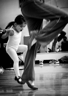 Adorable little girl learning to tap dance.