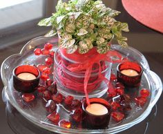 Cheap and Easy Cute Valentine's Day Centerpiece! Live Polka Dot plant (easy care plant); Dollar Store votives, candle holders, table scatter and metal vase; used ribbon from a package; glass tray I already owned! Once the weather  is warmer the plant will be outside in the garden :)