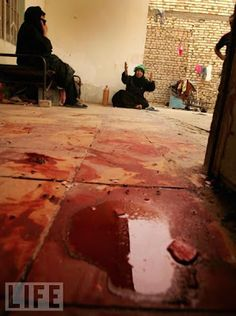 Blood is seen as Iraqi women cry for their relatives killed in an alleged U.S air strike on April 8, 2008 in the Sadr City district of Baghdad, Iraq.