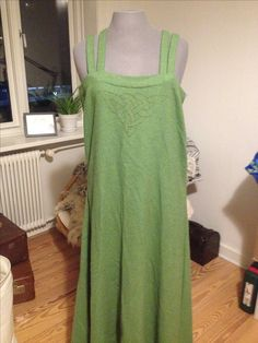 Aprondress. Green wool with embroidery on the front chest. Machine and handsewn.
