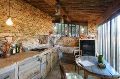 Une cuisine rustique parée de pierres et de bois