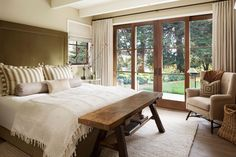 The master bedroom boasts striped pillows and wooden sliding glass doors.