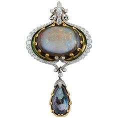 An American Art Nouveau 18 karat gold and platinum brooch/pendant with black opal, diamonds and enamel by Marcus & Co. The brooch/pendant has a center cabochon opal and 76 old mine-cut diamonds with an approximate total weight of 4.00 carats. Circa 1900. 1stdibs.com