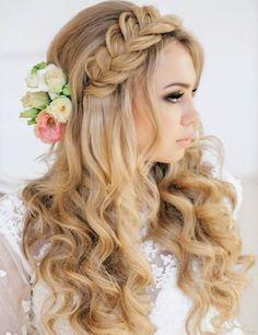 Bonito peinado medio recogido con trenza, flores y el pelo suelto rizado. Un peinado femenino moderno perfecto para la boda.