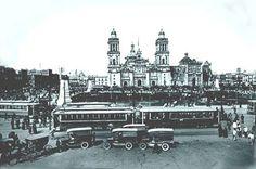 Para 1920 la Revolución había terminado y México volvía a crecer con celeridad. Esta imagen muestra el intenso movimiento de pasajeros en las terminales de tranvías que se encontraban en el costado sur de la plaza, al igual que la proliferación de vehículos a gasolina y una que otra carretela de tracción animal. El Zócalo está completamente despejado y sin árboles, de acuerdo con la idea de permitir el lucimiento de los edificios que lo rodean. En este año se instalan 4 esculturas de bronce…