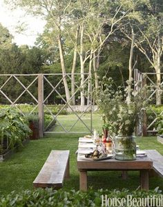 Picturesque Outdoor Dining:  Rustic yet refined, a 10-foot-long table and benches welcome guests to the calm center of landscape designer Lisa Bynon's vegetable and cutting garden in Southampton, New York. The Belgian oak furniture, Tuscan stoneware, handblown goblets, vase, and linen napkins all come from Bloom, the Sag Harbor tabletop and antiques shop of Bynon's partner, Mona Nerenberg.