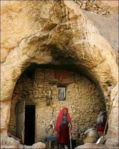 A woman from the ethnic Hazara minority stands in front of her cave home in Bamiyan, some 240 km (150 miles) northwest of Kabul, Afghanistan.
