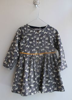 Snow-drop print grey dress with mustard yellow ribbon tie.