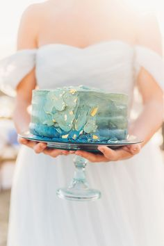wedding cake with gold leaf - photo by Michelle Roller Photography http://ruffledblog.com/windswept-bridal-editorial-on-the-beach #weddingcake #cakes