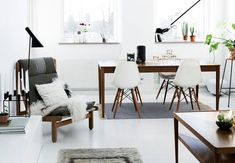 Here's one lovely renovated Danish family home. The style is vintage-inspired with modern setting. Simple living room has white painted floor, different hues of grey, warm wood and a Flos