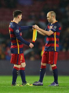 Andres Iniesta (R) of Barcelona passes the captain's armband to his team mate Lionel Messi (L) as he is replaced during the UEFA Champions League round of 16, second Leg match between FC Barcelona and Arsenal FC at Camp Nou on March 16, 2016 in Barcelona