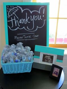 BEFORE: Thank you sign and baby shower favors - Poppin' whipped cream vodka mini bottles and assorted chocolates wrapped in blue.  Check out the after at http://projectnursery.com/projects/baby-kanes-nursery/