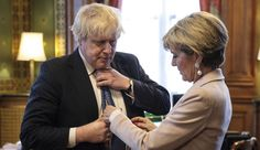 British Foreign Secretary Boris Johnson has his tie straightened by his Australian counterpart Foreign Minister Julie Bishop in his office