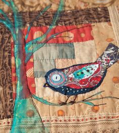 A log cabin block ... embellished with applique, hand and machine embroidery, and a little paint.