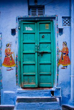 This is fabulous! green door on blue wall w. painted figures