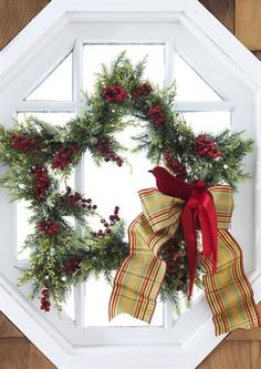 ≈star wreath with greenery and red berries, bow and red bird. I can see this with a bit of grapevine for structure, and I can also see it in heart shape, or any other. very close to being at home in a rustic setting, make the bow homespun maybe. :)