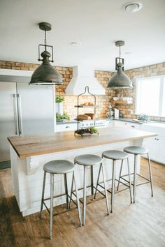 white kitchen with brick wall and large metal pendant lights - love this industrial farmhouse kitchen look.