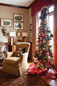 Use a super-skinny tree when space is at a premium. This tree, located in a gentleman's study, is tall, slender and adorned with colored lights and ornaments that give it a masculine feel.