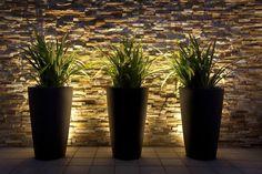 Colocar una lámpara detrás de cada maceta acentuará los volúmenes y los colores de tu patio. ¡Anímate a probarlo!