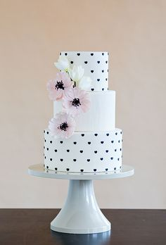 Brides: Black-and-White Polka Dot Wedding Cake. Instead of Swiss dots or polka dots, cake designer Erin Gardner of Wild Orchid Baking Co. decorated the tiers with tiny fondant hearts, which gives the design a preppy-yet-whimsical feel. She finished off the design with gumpaste pink poppies and wafer-paper tulips.