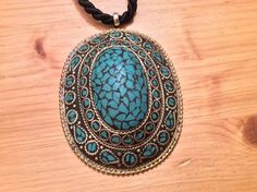 """A splendid old ( early 20th century) pendant in brass and turquoises coming from Tibet...marquetry on the top and very nice plaiting settings for all the other turquoises ...actually for sale in my shop at 28,Galerie du Roi at 1000 Brussels and very soon on my website www.halter-ethnic.com under the item """"My Lucky Finds"""". the black cord and the clasp are new... The hook is in silver..."""