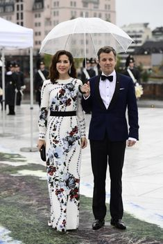 Crown Princess Mary looked stunning in a floor length white gown. Crown Prince Frederik of Denmark ensures Crown Princess Mary stays dry as they arrive at the gala dinner.