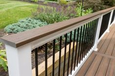 A capped composite deck built from Trex in Spiced Rum, with matching fascia, white vinyl railing with black aluminum balusters and a matching deck board on the railing. Vinyl Deck Railing, Front Porch Railings, Deck Railing Design, Patio Railing, Patio Deck Designs, Vinyl Pergola, Deck With Pergola, Pergola Ideas, Patio Roof