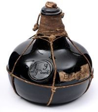 An early onion shaped wine bottle,imprinted with GC, circa 1690. Initially made exclusively for 'gentlemans' cellars, wine merchants and some of the better city taverns, wine bottles were dark green in colour, almost black. The aim with their colour was probably to strike a balance between protecting the contents from sunlight and being able to see the contents.