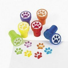 """24 Paw Print Stampers (887600880542) You will receive 4 factory sealed sets of 6 stampers. Each set of 6 contains one stamper of each color as shown. A total of 24 stampers. Each stamper measures 1.5"""" x 1"""" Great for crafting, scrapbooking and adorning letters and postcards as well. Safe and non-toxic. 24 stampers with paw prints. Set the tone for your dog or cat's birthday party, your fundraiser, shelter event or any other animal-themed event with these multi-colored, self-inking stampers."""