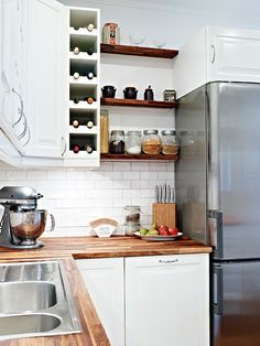 Lovely kitchen features crisp white cabinets paired with wood countertops and subway tiled backsplash. This is what I was thinking to add on end of upper cabs except perhaps just a single vertical row of small cubs.