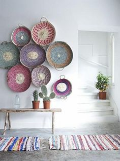 Colorful baskets displayed as wall art - great idea for a beach house!