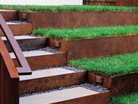 Task lit stairs are made from cast concrete and are set in gravel with grass terraces as steps ascend to upper levels of the garden.