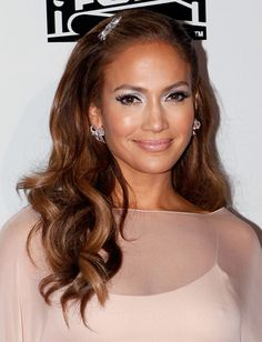 Need a fresh take on your typical half-up, half-down hairstyle? Jennifer Lopez's 'do is totally easy to reproduce, flatters every face shape and the side-part and hair accessory totally up the glam factor. #hairstyle #spring