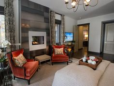 A purely modern fireplace surround is the focal point on this side of the room. Burnt orange armchairs create a cozy spot to enjoy the flame.  http://www.hgtv.com/dream-home/master-bedroom-pictures-from-hgtv-dream-home-2014/pictures/page-7.html?soc=pindhm