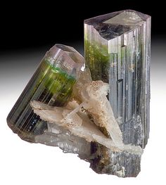 tri-color Tourmaline crystals with Albite,  Both crystals are held tight by several blades of Cleavelandite.  From Paprok, Nuristan Province, Afghanistan.  Measures 3.3 cm by 2.7 cm by 2 cm in total size.  Ex. Webb Mineral Collection